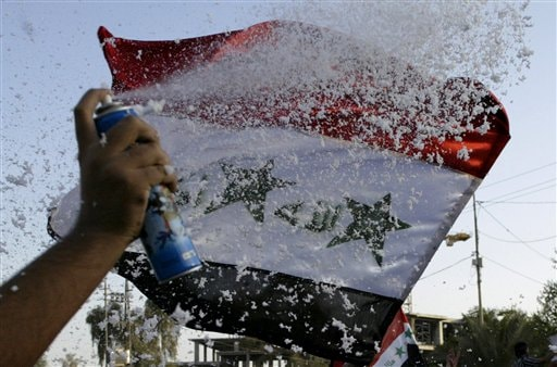 An Iraqi man sprays confetti during celebrations for their national soccer team victory in the Asian Cup, in streets of the Shiite holy city of Najaf, 160 kilometers (100 miles) south of Baghdad, Iraq, Sunday, July 29, 2007. Iraqi national soccer team defeated Saudi Arabia 1-0 in the Asian Cup soccer final played in Jakarta.