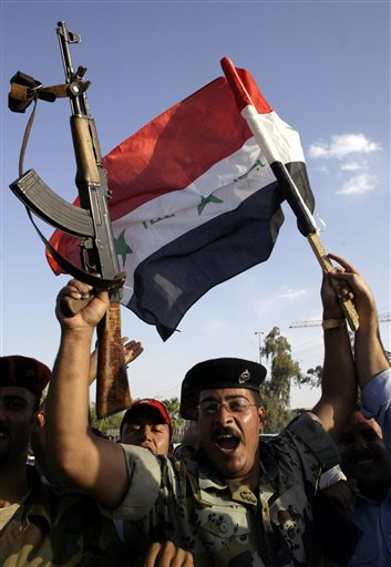 An Iraqi soldier celebrates Iraq's win in the Asian Cup final against Saudi Arabia in Najaf, 160 kilometers (100 miles) south of Baghdad, Iraq, Sunday, July 29, 2007. Iraq won the final after defeating Saudi Arabia 1-0 in Jakarta.