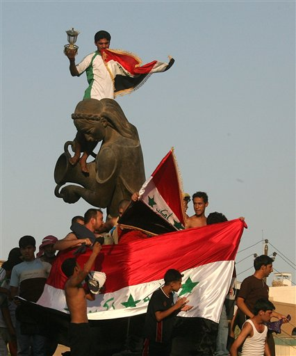 People with Iraqi flags, gathered around statue of Kharmana, celebrate in streets of central Baghdad, Iraq, Sunday, July 29, 2007. Iraqi national soccer team defeated Saudi Arabia 1-0 in the Asian Cup soccer final played in Jakarta.