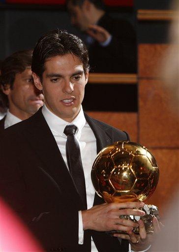 Kaka arrives for a photocall holding the Golden Ball award.
