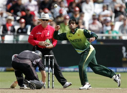 Pakistan's bowler Mohammad Hafeez, right, fields off his own bowling as New Zealand's batsman Daniel Vettori, left, avoids the play whilst umpire Daryl Harper of Australia, center, looks on during their semifinal in the Twenty20 World Championship at the Newlands Stadium in Cape Town, South Africa, Saturday, Sept. 22, 2007.