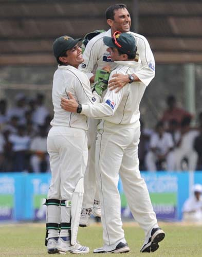 Younus Khan is congratulated by teammate wicketkeeper Kamran Akmal and Misbah-ul-Haq after the dismissal of Tillakaratne Dilshan during the third day of the first Test match between Pakistan and Sri Lanka at The Galle International Stadium in Galle. (AFP Photo)