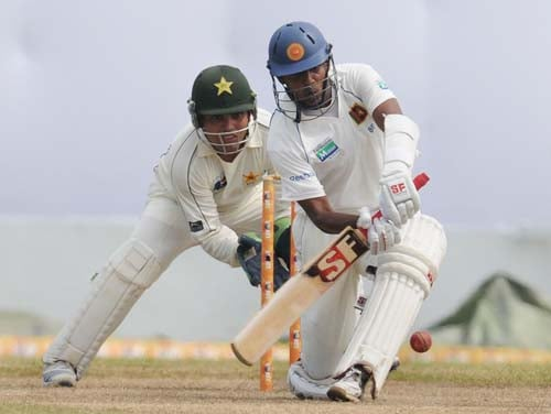 Thilan Samaraweera plays a shot as Kamran Akmal looks on during the third day of the first Test match between Pakistan and Sri Lanka at The Galle International Stadium in Galle. (AFP Photo)