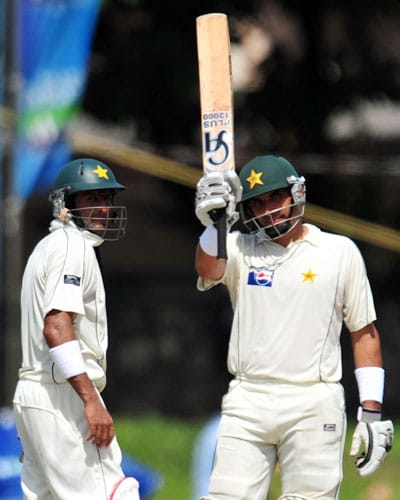 Misbah-ul-Haq raises his bat to the crowd after scoring a half-century as Shoaib Malik looks on during the third and final Test match between Sri Lanka and Pakistan at The Sinhalese Sports Club in Colombo. (AFP Photo)