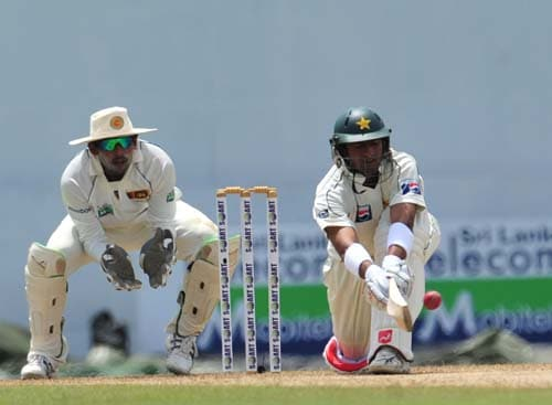 Shoaib Malik bats as Tillakaratne Dilshan looks on during the first day of the second Test match between Pakistan and Sri Lanka at The P. Saravanamuttu Stadium in Colombo. (AFP Photo)