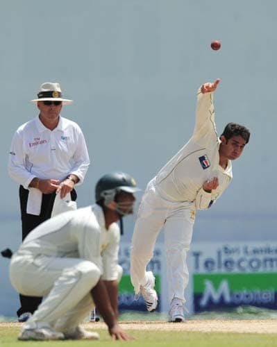 Saeed Ajmal delivers the ball as Australian umpire D.J. Harper looks on during the second day of the second Test match between Pakistan and Sri Lanka at The P. Saravanamuttu Stadium in Colombo. (AFP Photo)
