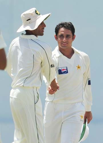 Saeed Ajmal is congratulated by his teammate Younus Khan after dismissing Angelo Mathews during the second day of the second Test match between Pakistan and Sri Lanka at The P. Saravanamuttu Stadium in Colombo. (AFP Photo)