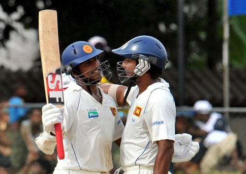 Malinda Warnapura is congratulated by teammate Kumar Sangakkara after scoring a half-century during the third day of the second Test match between Pakistan and Sri Lanka at The P. Sara Oval Stadium in Colombo. (AFP Photo)
