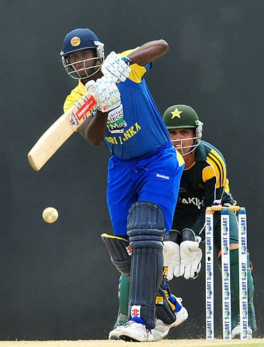 Angelo Mathews is watched by Kamran Akmal as he plays a shot during the first One-Day International match between Sri Lanka and Pakistan in Dambulla. (AFP Photo)