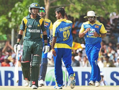 Nuwan Kulasekara celebrates with his teammates after dismissing Shoaib Malik during the first One-Day International match between Sri Lanka and Pakistan in Dambulla. (AFP Photo)