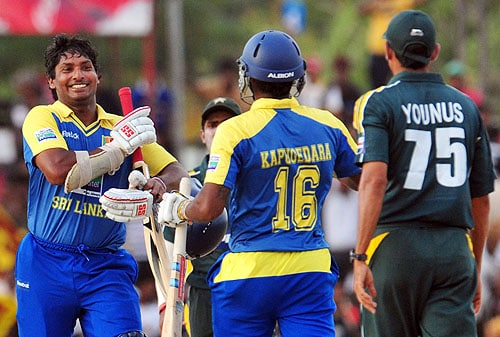Kumar Sangakkara celebrates victory with teammate Chamara Kapugedara as Younus Khan looks on at the end of the third One-Day International match between Sri Lanka and Pakistan at The Rangiri Dambulla International Cricket stadium in Dambulla on August 3, 2009. Sri Lanka defeated Pakistan by six wickets to take an unbeatable 3-0 lead in the five-match one-day series. (AFP Photo)