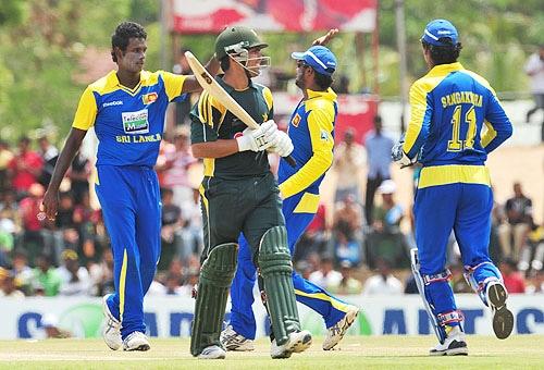 Angelo Mathews celebrates with teammates Chamara Kapugedera and Kumar Sangakkara after dismissing Kamran Akmal during the third One-Day International match between Sri Lanka and Pakistan at The Rangiri Dambulla International Cricket stadium in Dambulla. (AFP Photo)