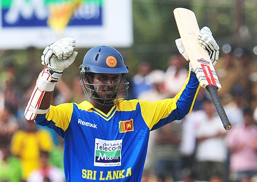 Upul Tharanga raises his bat in the air to celebrate scoring a half-century during the third One-Day International match between Sri Lanka and Pakistan at The Rangiri Dambulla International Cricket stadium in Dambulla. (AFP Photo)