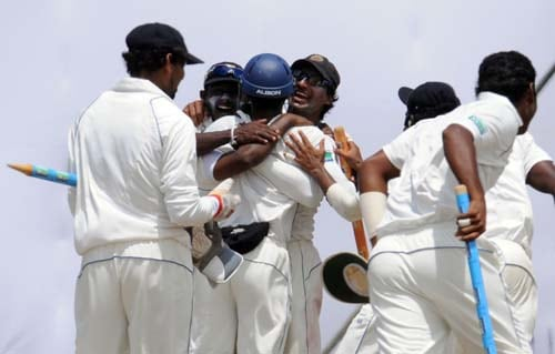 Sri Lankan cricketers celebrate their team's victory with Kumar Sangakkara at the conclusion of the fourth day of the first Test match between Pakistan and Sri Lanka at The Galle International Stadium in Galle. (AFP Photo)