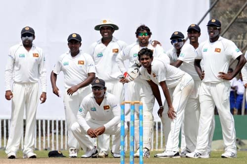Sri Lankan cricketers look on as they wait for a decision from the third umpire for the wicket of Misbah-ul-Haq during the fourth day of the first Test match between Pakistan and Sri Lanka at The Galle International Stadium in Galle. (AFP Photo)