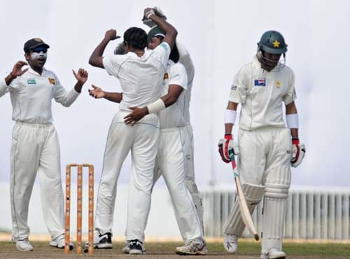 Thilan Thushara celebrates with teammates after the dismissal Shoaib Malik during the fourth day of the first Test match between Pakistan and Sri Lanka at The Galle International Stadium in Galle. (AFP Photo)