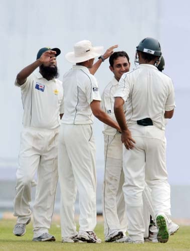 Mohammad Aamer is congratulated by his teammates after dismissing Thilan Thushara during the first Test match between and Sri Lanka at The Galle International Stadium. (AFP Photo)
