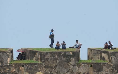 A Sri Lankan security official stands guard on the 16th Century Dutch fort overlooking The Galle International Stadium. (AFP Photo)