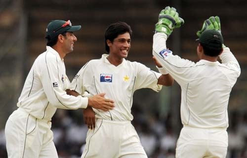 Mohammad Aamer is congratulated by teammates Kamran Akmal and Misbah-ul-Haq after dismissing Tillakaratne Dilshan during the first Test match between and Sri Lanka at The Galle International Stadium. (AFP Photo)
