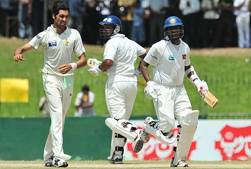Kumar Sangakkara and teammate Thilan Samaraweera run between the wickets as Umar Gul looks on during the final day of the third Test match between Sri Lanka and Pakistan at The Sinhalese Sports Club in Colombo. (AFP Photo)