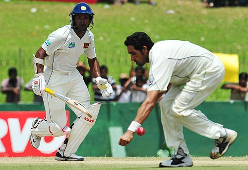Kumar Sangakkara runs between the wickets as Umar Gul dives as he fields a ball during the fifth day of the third Test match between Sri Lanka and Pakistan at The Sinhalese Sports Club in Colombo. (AFP Photo)