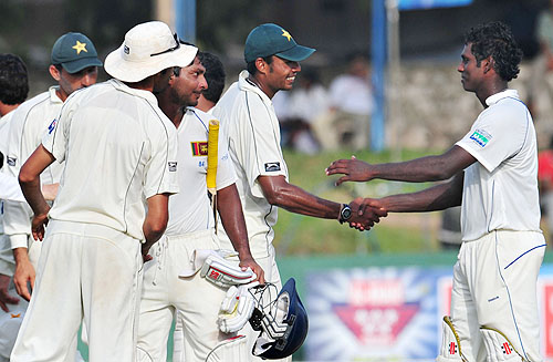 Kumar Sangakkara shakes hands with Umar Gul following the final Test match between Sri Lanka and Pakistan at The Sinhalese Sports Club in Colombo. (AFP Photo)