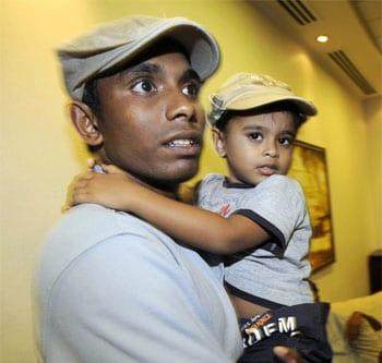 Sri Lankan cricketer Thilina Thushara Mirando holds his son upon his return to the island on March 4. All Sri Lankan players, including those who got injured during the attack, are safe now. (AFP)
