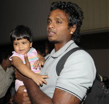 Sri Lankan cricketer Dilhara Fernando holds his daughter after returning to Colombo after escaping the attack that took place in Gulberg, an upmarket area of Lahore, at around 9 am on March 3 as the Lankan team made their way to the stadium for the third day's play in the second Test against Pakistan. (AFP)