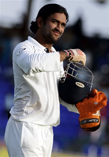 India's wicket keeper Mahendra Dhoni smiles as he walks off the field on the first day of the third cricket test match against the West Indies at St. Kitts.