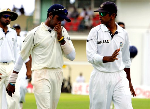 India bowler S Sreesanth, left, talks with captain Rahul Dravid, as they walk off the field when rain stopped play on the first day of the third cricket test match at St. Kitts.