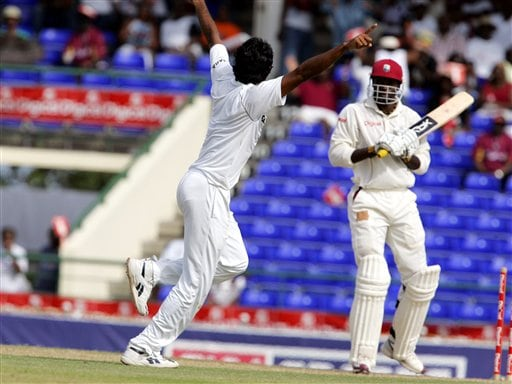 India's bowler Munaf Patel, left, celebrates after bowling West Indies batsman Chris Gayle, right, for 143 for 1 on the first day of the third cricket test match at St. Kitts.
