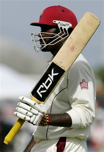 West Indies opening batsman Chris Gayle raises his bat as he walks off the field after being bowled by India's bowler Munaf Patel on the first day of the third cricket test at St. Kitts.