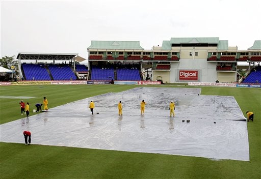 Grounds crew adjust a tarp on the pitch after heavy rains fell, canceling afternoon play on the second day of the third cricket test match bewteen the West Indies and India at St. Kitts.