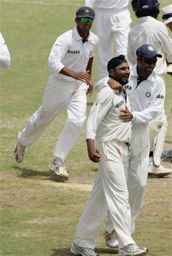 India's bowler Harbhajan Singh, centre, is congratulated by Mohammad Kaif, right, after Singh took five wickets to end the West Indies first innings at 581 for 10 on the third day of the third cricket Test match at Warner Park in Basseterre, St Kitts, Saturday, June 24, 2006. At left is captain Rahul Dravid. (AP Photo/Lynne Sladky)