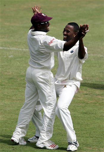 West Indies captain Brian Lara, left, celebrates with bowler Corey Collymore, right, after Lara caught Indian batsman Virender Sehwag off the bowling of Collymore for 61 for 1 on the third day of the third cricket Test match at Warner Park in Basseterre, St Kitts, Saturday, June 24, 2006. (AP Photo/Lynne Sladky)