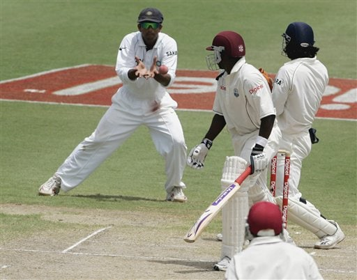 India's captain Rahul Dravid, left, makes a catch on a ball hit by West Indies batsman Pedro Collins, centre, for 581 for 9 off the bowling of India's bowler Harbhajan Singh on the third day of the third cricket Test match at Warner Park in Basseterre, St Kitts, Saturday, June 24, 2006. (AP Photo/Lynne Sladky)