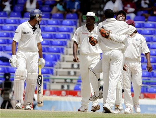 Indian batsman VVS Laxman, left, watches as West Indies wicketkeeper Denesh Ramdin, right, hugs bowler Pedro Collins, back to camera, after Laxman was caught off the bowling of Collins for 311 for 8 on the fourth day of the third cricket Test match at Warner Park in Basseterre, St Kitts, Sunday, June 25, 2006. (AP Photo/Lynne Sladky)