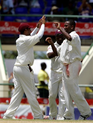 West Indies batsman Corey Collymore, right, is congratulated by Daren Ganga, left, and captain Brian Lara, centre, after taking the wicket of India's batsman Mahendra Dhoni LBW for 220 for 6 on the fourth day of the third cricket Test match at Warner Park in Basseterre, St Kitts, Sunday, June 25, 2006. (AP Photo/Lynne Sladky)