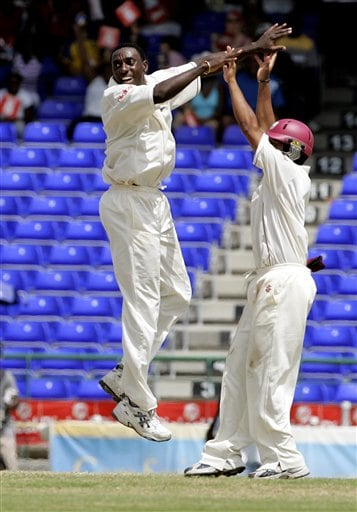 West Indies bowler Pedro Collins, left, celebrates with Ramnaresh Sarwan after taking the wicket of India's batsman Shanthakumaran Sreesanth for 315 for 9 on the fourth day of the third cricket Test match at Warner Park in Basseterre, St Kitts, Sunday, June 25, 2006. (AP Photo/Lynne Sladky)