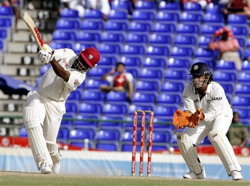 West Indies captain Brain Lara, left, hits a six off the bowling of India's bowler Anil Kumble (not shown) in the second inning on the fourth day of the third cricket Test match at Warner Park in Basseterre, St Kitts, Sunday, June 25, 2006. At right is India's wicketkeeper Mahendra Dhoni. (AP Photo/Lynne Sladky)