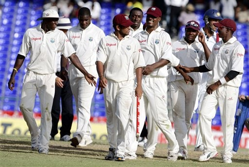 West Indies' Ramnaresh Sarwan, center, carries a piece of the stump, as he walks off the field with his teammates at the end of the third cricket test match against India at St Kitts.