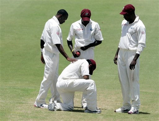 West Indies' Ramnaresh Sarwan, kneeling, is consoled by bowler Dwayne Bravo, left, after dropping a ball hit by India batsman Virender Sehwag on the fifth day of the third cricket test match at St Kitts.