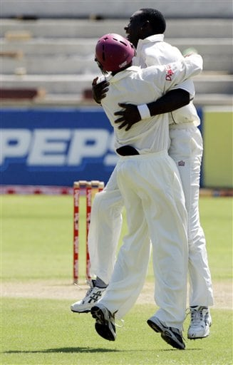 West Indies bowler Pedro Collins, right, hugs Ramanresh Sarwan, left, after Sarwan caught India's batsman Virender Sehwag for the first wicket during the fourth Test match at Kingston.