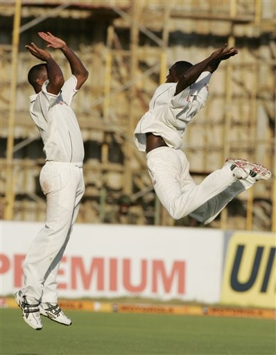 West Indies bowler Jerome Taylor, right, leaps into the air as he celebrates with Corey Collymore, left, after getting the wicket of India's Munaf Patel during the fourth cricket Test match at Kingston.