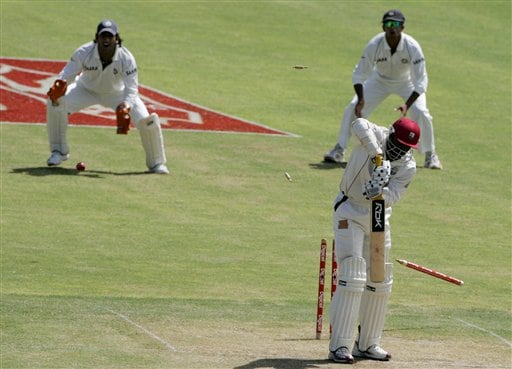 West Indies batsman Chris Gayle, right, is bowled for a duck by India's bowler S Sreesanth, not seen, for 0 on the second day of the fourth cricket Test at Kingston.