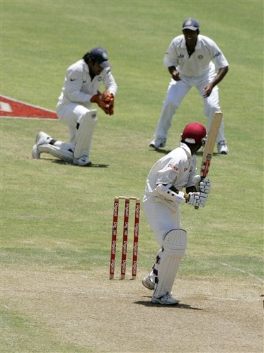 West Indies batsman Shivnarine Chanderpaul, right, looks back as he is caught by India's wickket keeper M S Dhoni, left, off the bowling of Munaf Patel on the second day of the fourth cricket Test at Kingston.