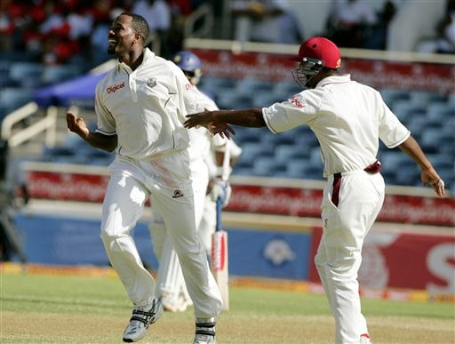 West Indies bowler Corey Colleymore, left, celebrates with Darren Ganga, right, after taking the wicket of India's batsman Yuvraj Singh on the second day of the fourth cricket Test at Kingston.