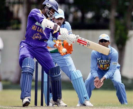 Sri Lankan cricketer Upal Tharanga, left, who scored 88, bats as India's Mahendra Dhoni, center, and Rahul Dravid look on during a practice match against Sri Lanka A, in Colombo.