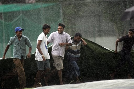 Ground staff of the Colombo Colts cricket ground rush with the rain covers after rain stopped play for a while, during a practice match against Sri Lanka A, in Colombo.