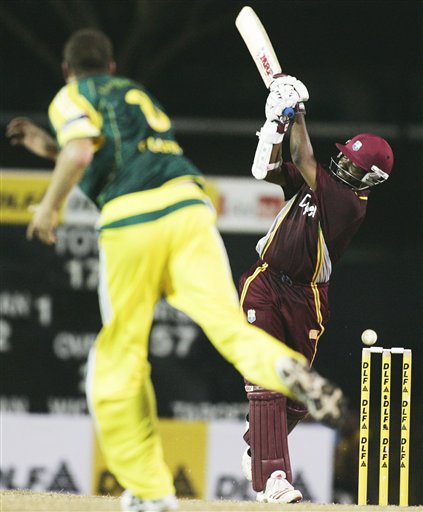 West Indies's batsman Chris Gayle, right, swipes at and misses a delivery from Australia's Stuart Clark in their tri-series match in Kuala Lumpur on Monday.